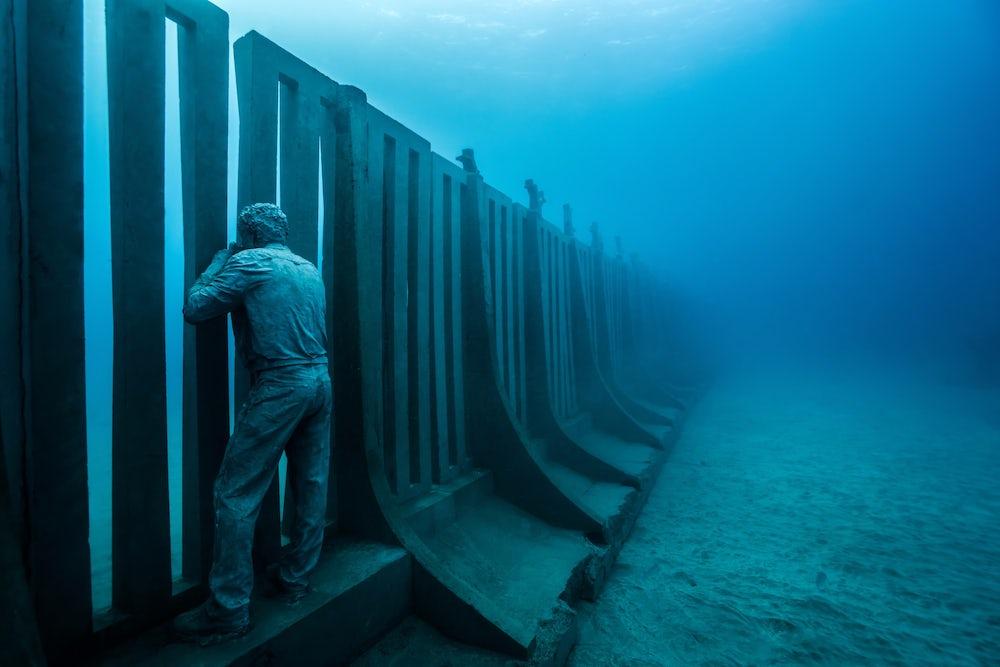 A photographer peeks through a gap in the wall.