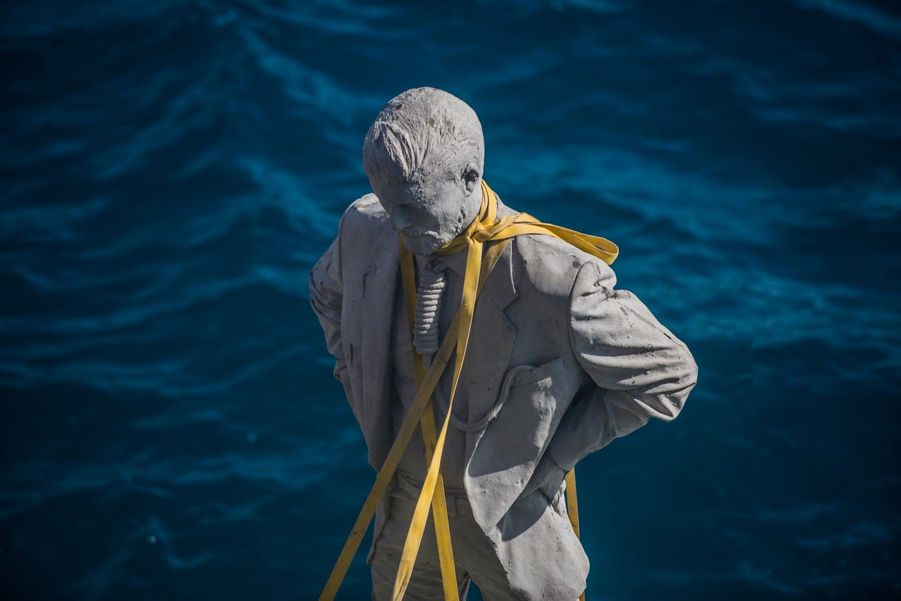 A statue is prepared to be lowered to the ocean floor.