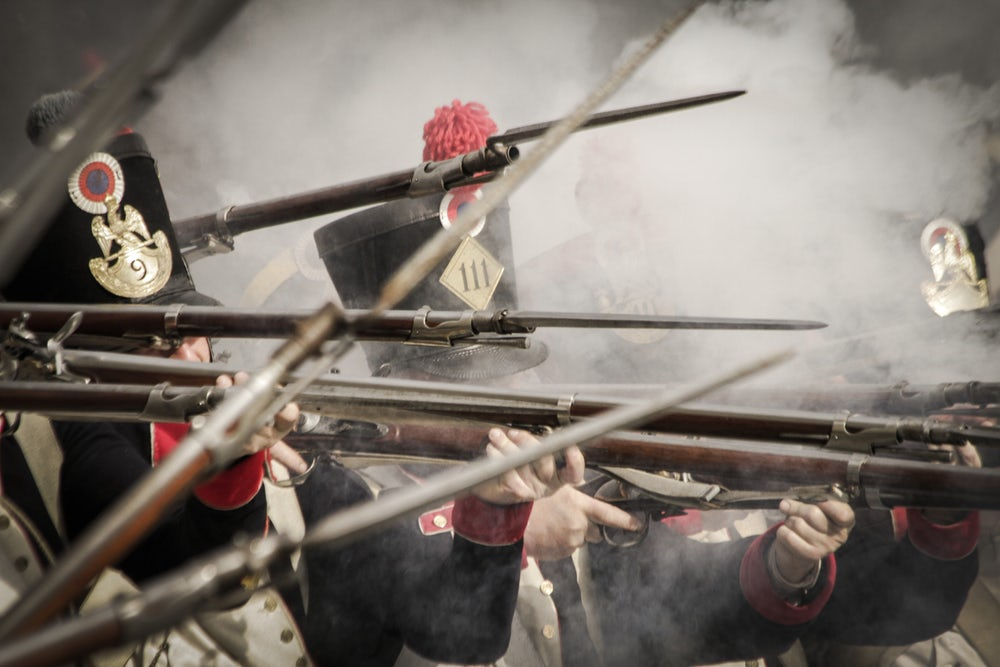 Soldiers of the French line infantry firing their weapons during a historical reenactment of the Napoleonic wars of the 19th century.
