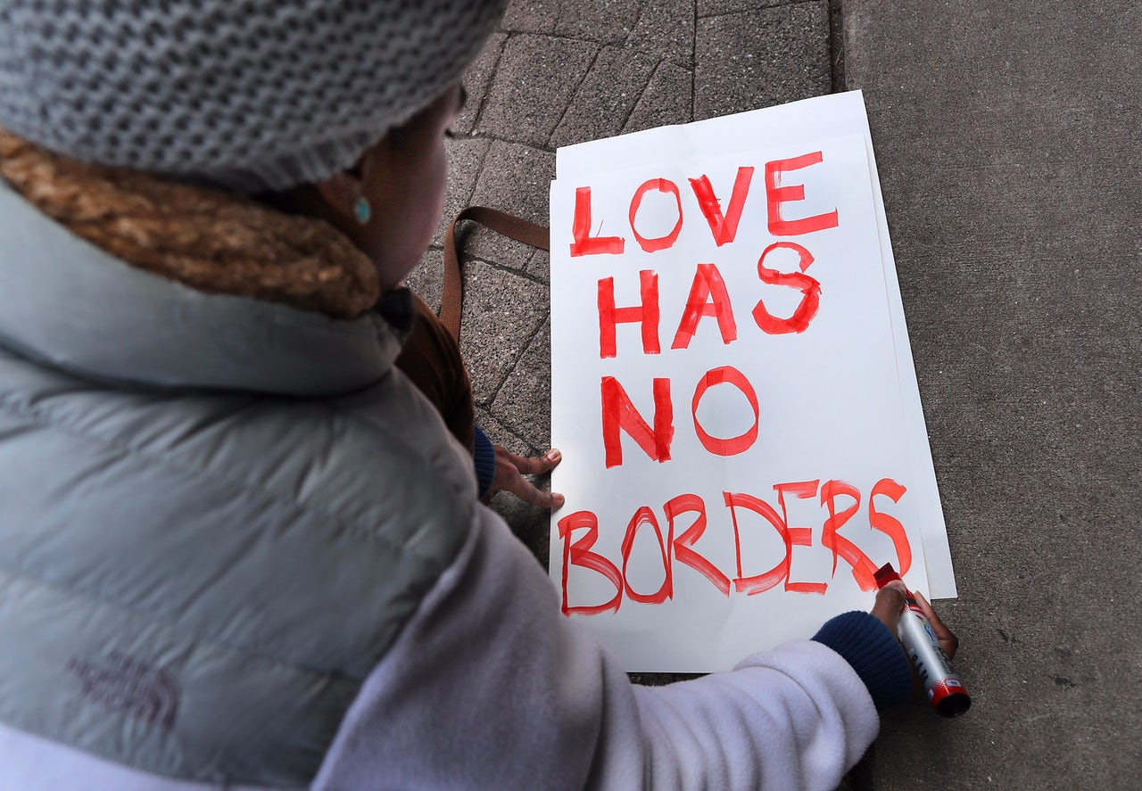 Tori Furtado, from Boston, kneels down to write a sign that reads, 'Love has no borders.'