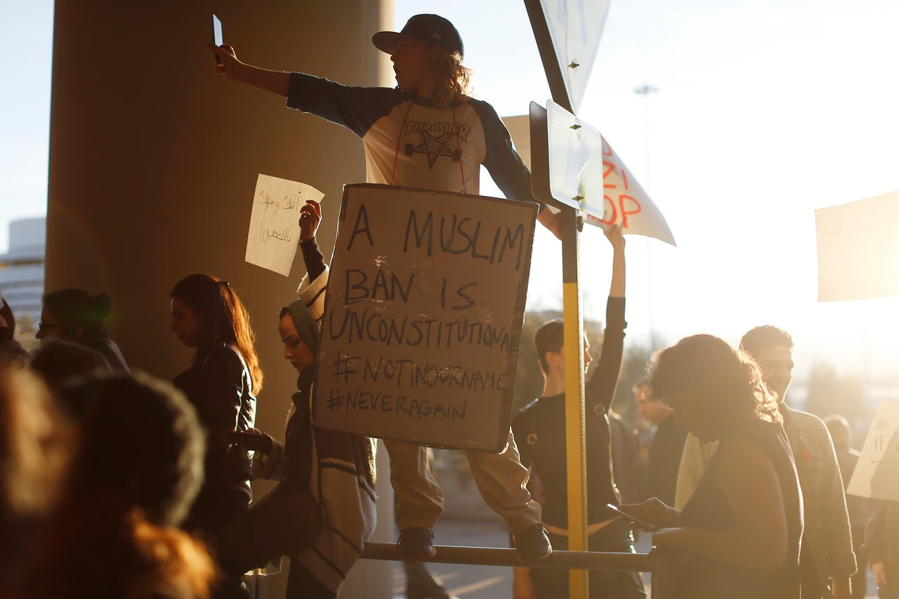 A demonstrator takes a photograph during a rally against Muslim immigration ban at San Francisco International Airport.