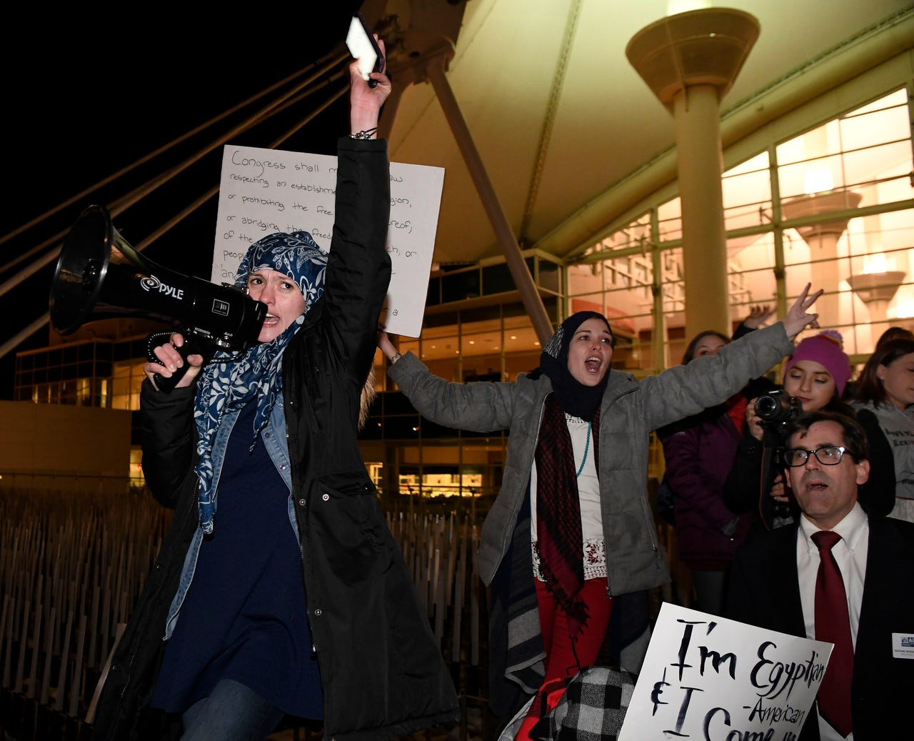Amal Kassir, a Syrian American, leads the crowd during an immigration protest at Denver International Airport.