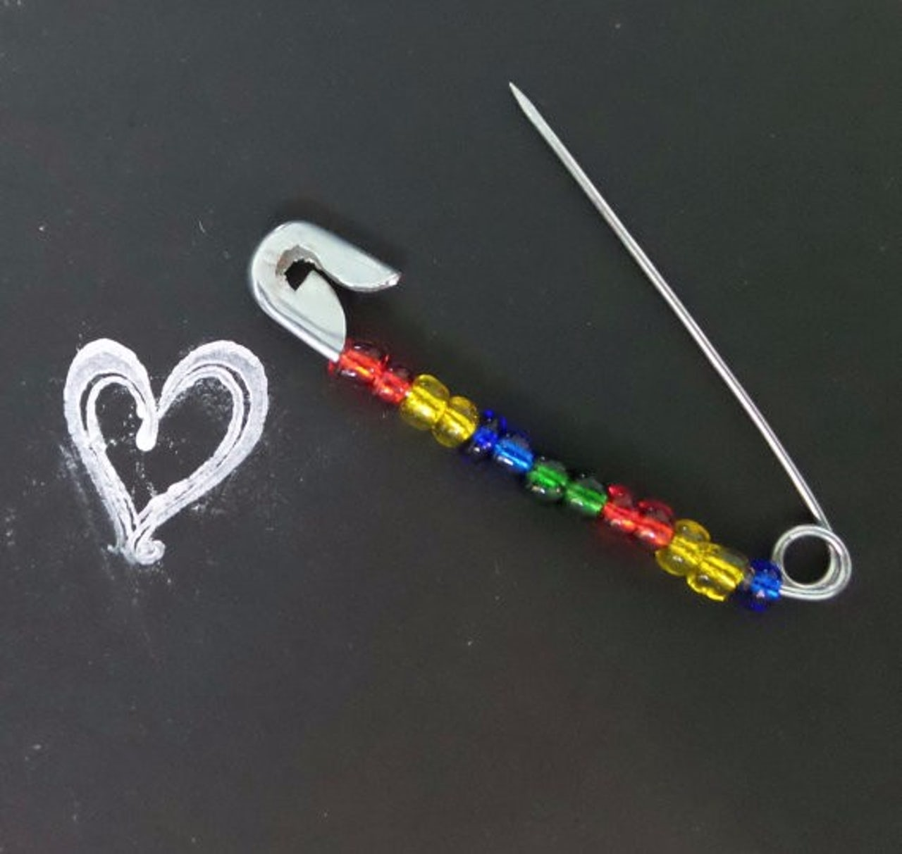 An LGBTQ-themed safety pin. The shop also has safety pins for expressing solidarity with Jews, Native Americans, and others.