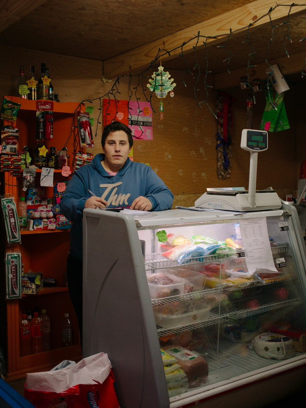 Augustine works as a clerk in one of the few shops inside the occupied Dos Banderas neighborhood, in the middle of the woods.