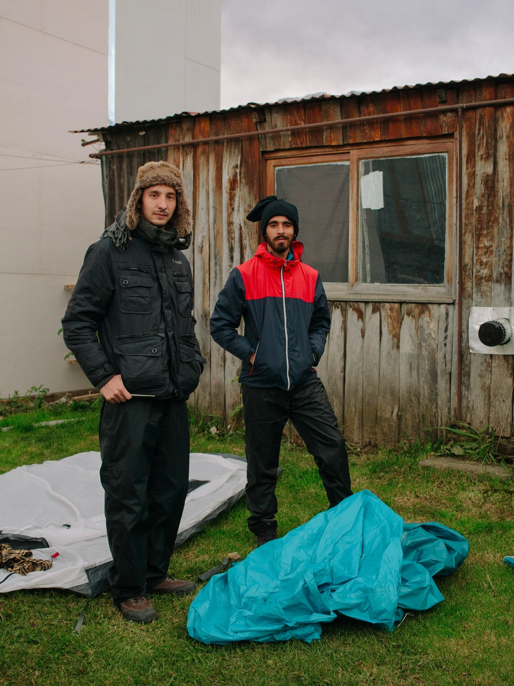 Ivan and Joao, two backpackers from Brazil setting up a tent in a private garden. Due to the cost of accommodations in Ushuaia, many turn to alternative ways of traveling.