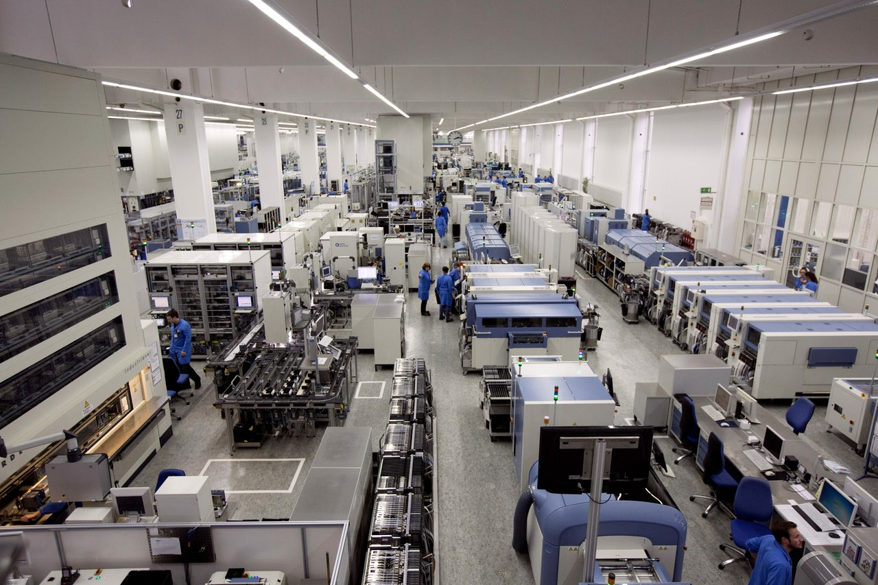 Employees work on the automated assembly line at the Siemens AG electronics factory in Amberg, Germany.