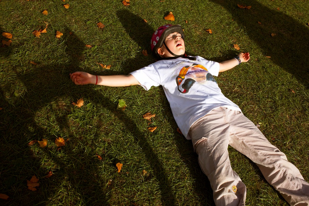 A young cyclist enjoys the grass grass at Peckham Rye Park in South London.