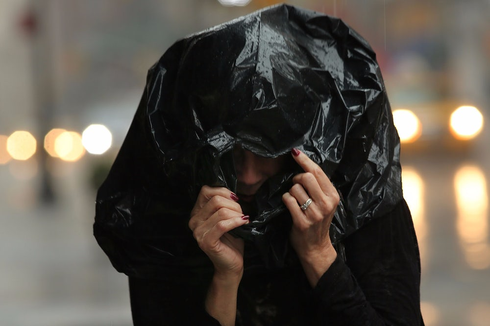 A woman shields herself from rain in New York City.