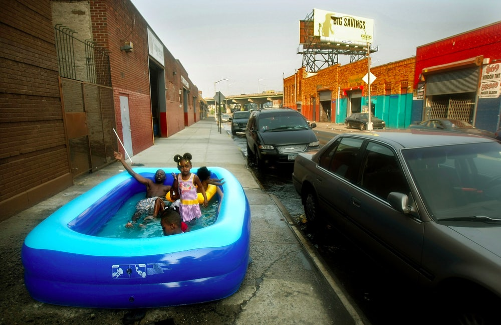 New Yorkers enjoy an inflatable pool on a sidewalk in the Bronx.