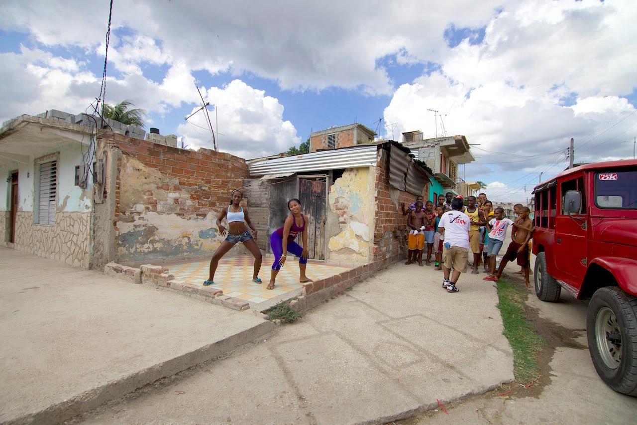 Young women dance in the streets of Santiago de Cuba.