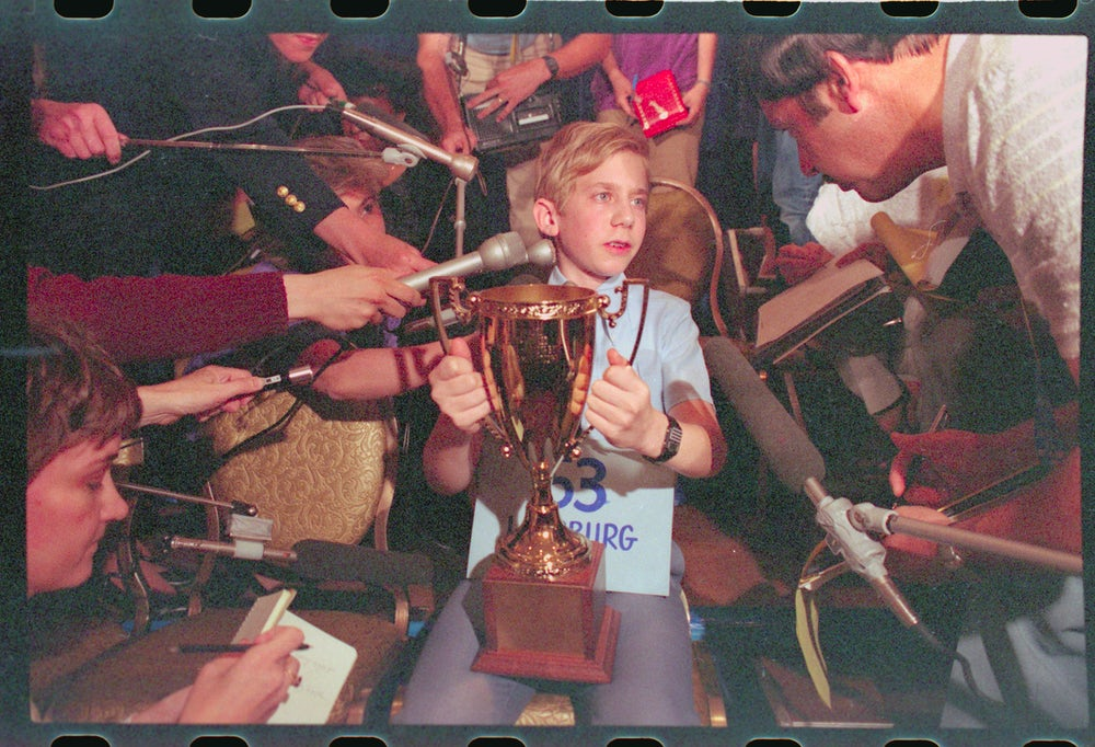 The 1984 Scripps National Spelling Bee winner, 13-year-old Daniel Greenblatt, shows off his trophy to gathered reporters.