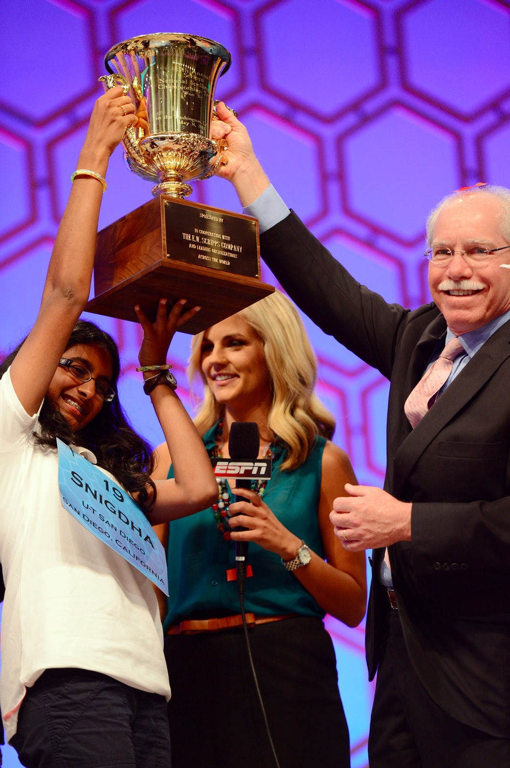 2012 Scripps National Spelling bee winner Snigdha Nandipati raises her trophy with Rich Boehne, President and CEO of The E.W. Scripps Company.