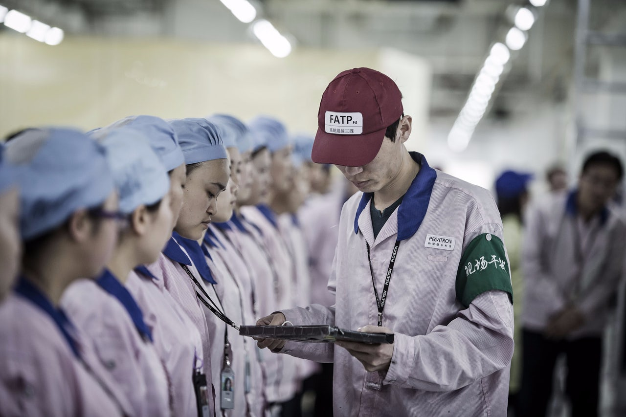 A supervisor holding an Apple Inc. iPad checks an employee's badge during roll call at a Pegatron Corp. factory in Shanghai, China.