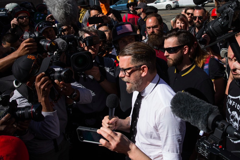 A member of the Proud Boys stands behind Gavin McInnes in a black and yellow Fred Perry polo, at a rally in Berkeley, California.