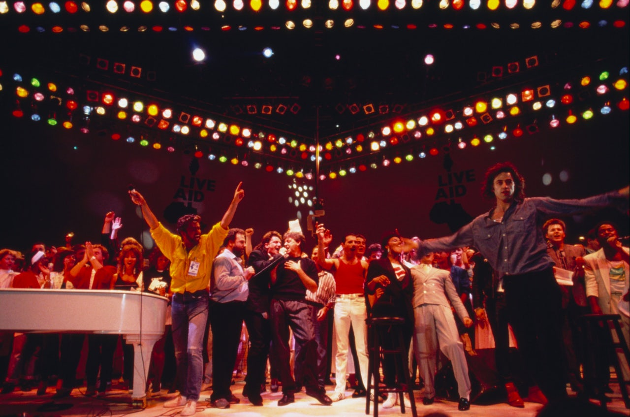 Bob Geldof (right with arms outstretched) onstage with performers at Live Aid at Wembley Stadium in 1985.