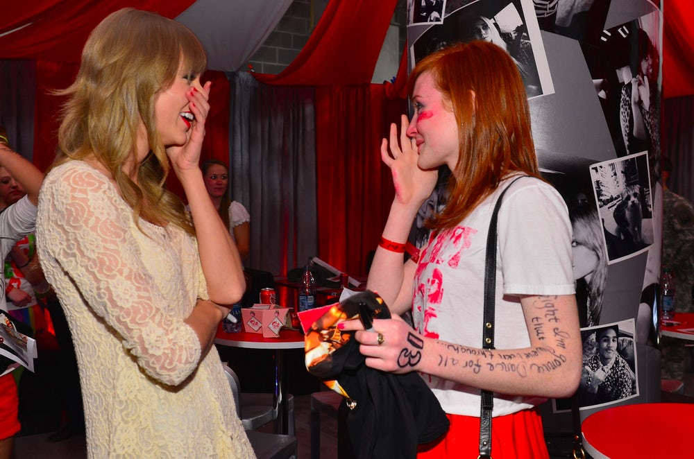 A fan wipes away tears while meeting Taylor Swift in 2013.