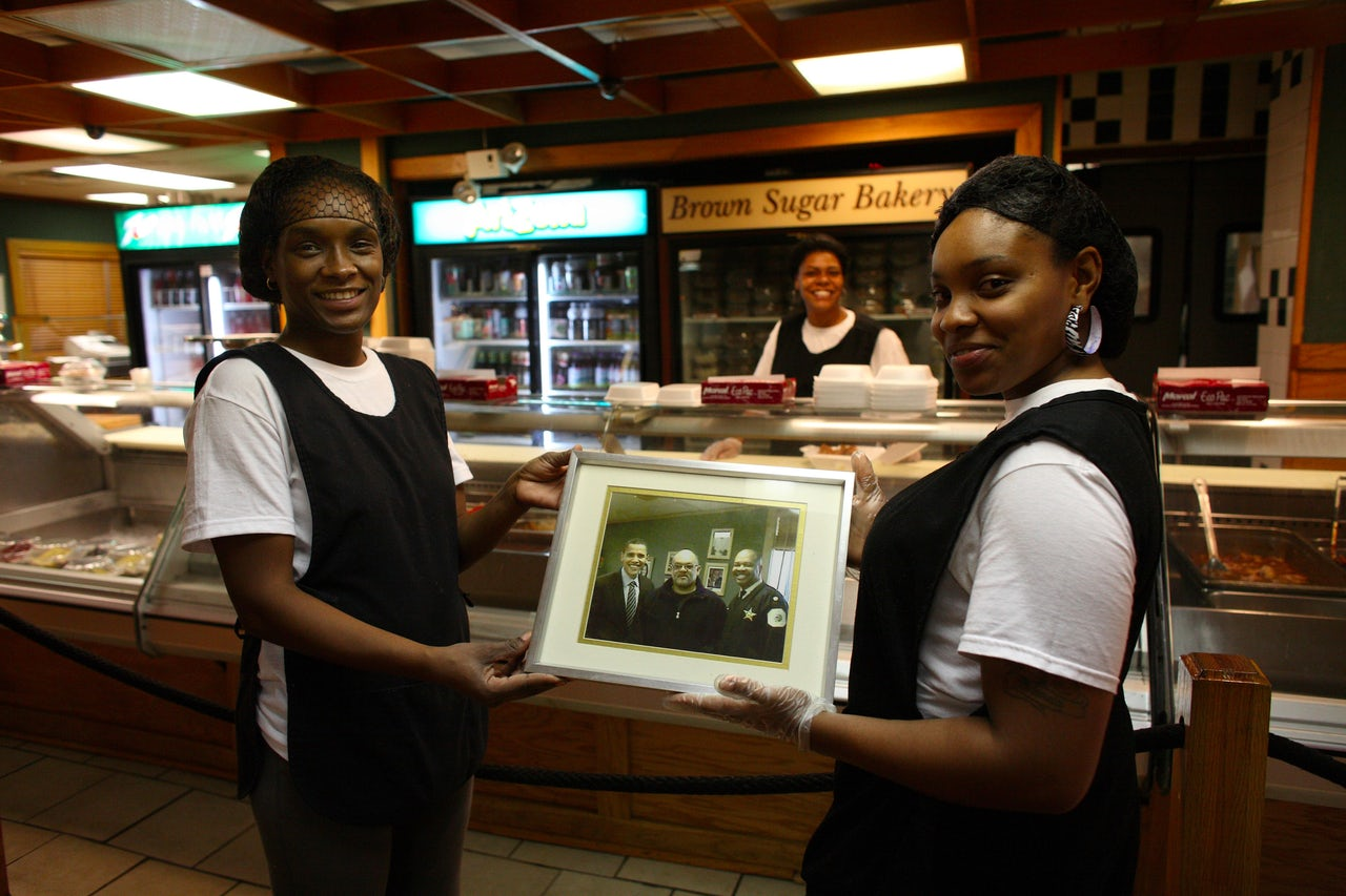 Servers at MacArthur's Restaurant in Chicago hold a photo featuring then-senator Barack Obama. Templeton credits Obama with drawing attention to black-owned restaurants.