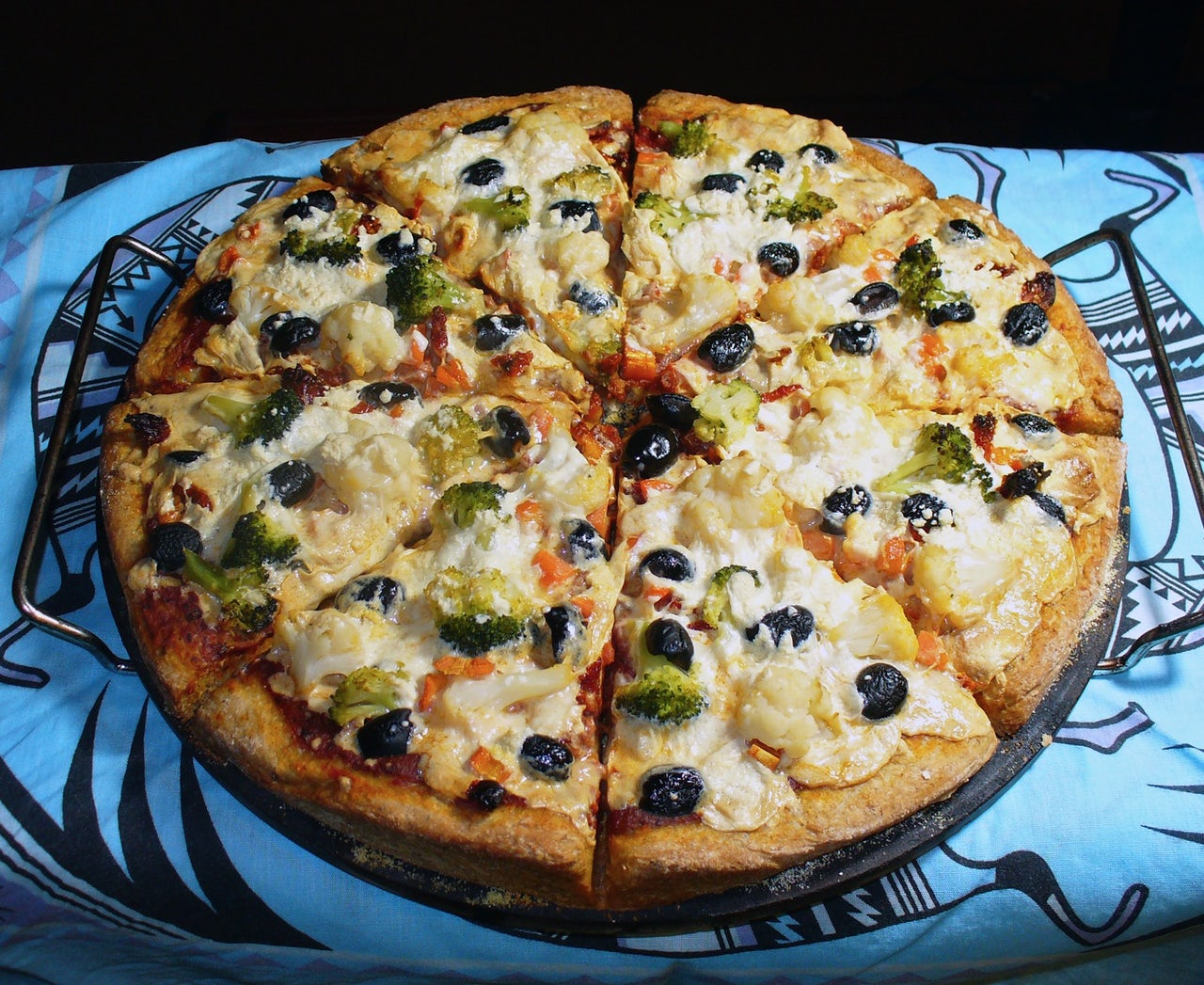 A homemade veggie lover's pizza with broccoli, cauliflower, carrots, sundried tomatoes, black olives, red sauce, and mozzarella Daiya cheese.