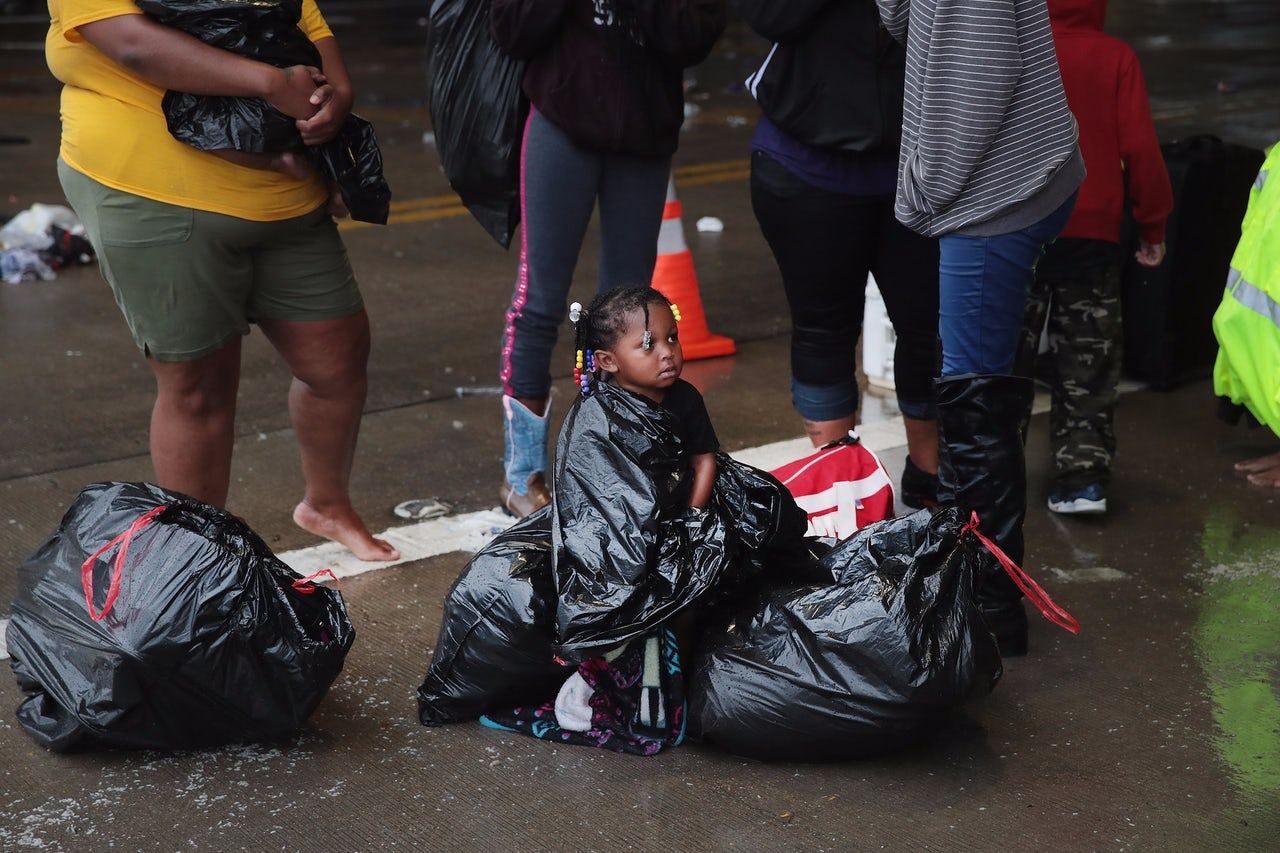Houston residents with their belongings in trash bags outside a flooded neighborhood in Houston.