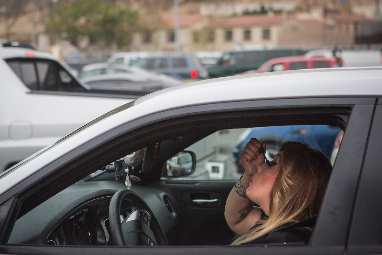 A woman does her makeup while waiting in the traffic at the San Ysidro border crossing.