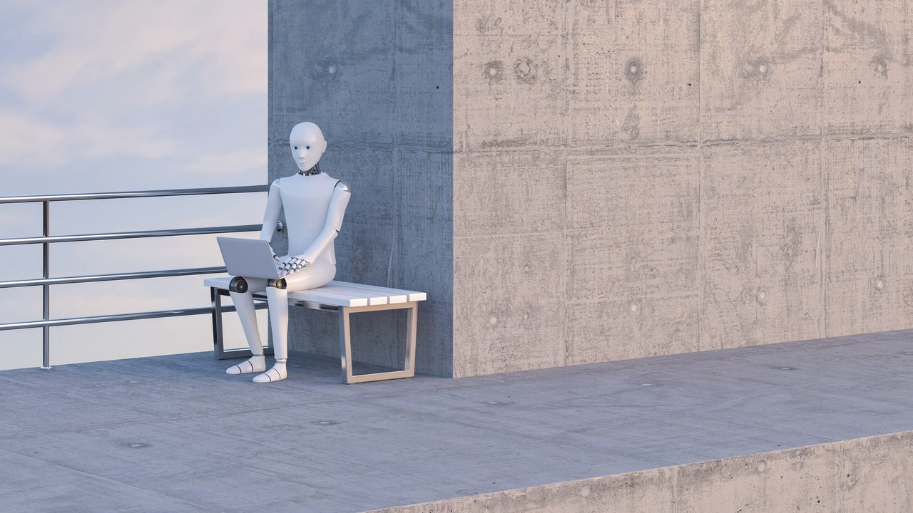 Robot sitting on bench, using laptop.