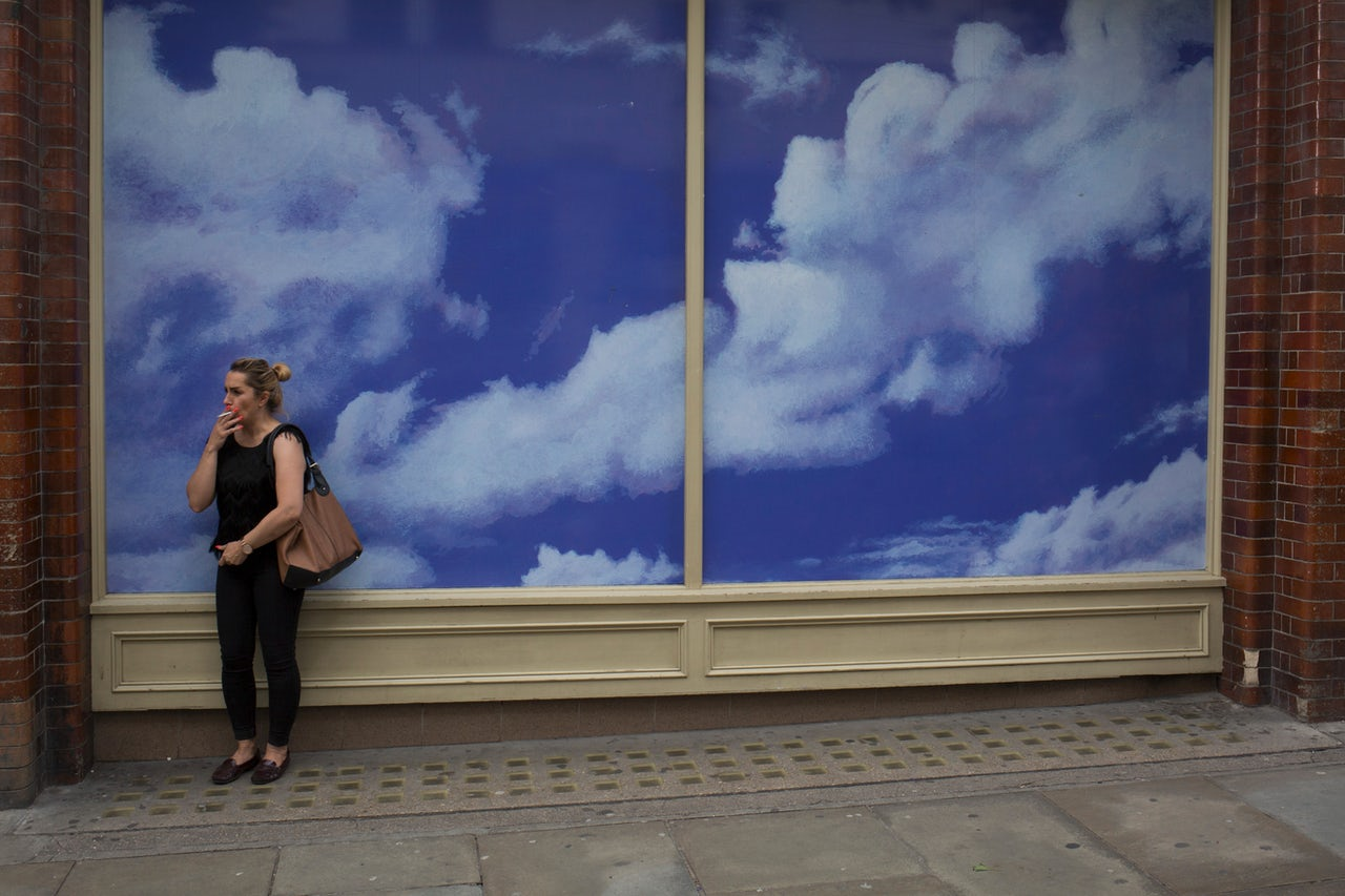 A smoker stands in front of a construction hoarding featuring cloud and sky patterns, on July 31, 2017, in Covent Garden, London, England.