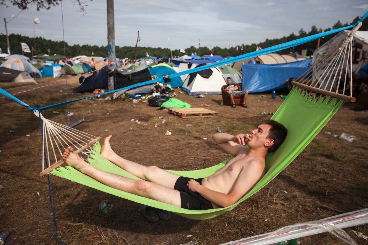 A man is seen smoking a cigarette on a hammock at the 2017 Woodstock Festival Poland on August 4, 2017 in Kostrzyn, Poland.
