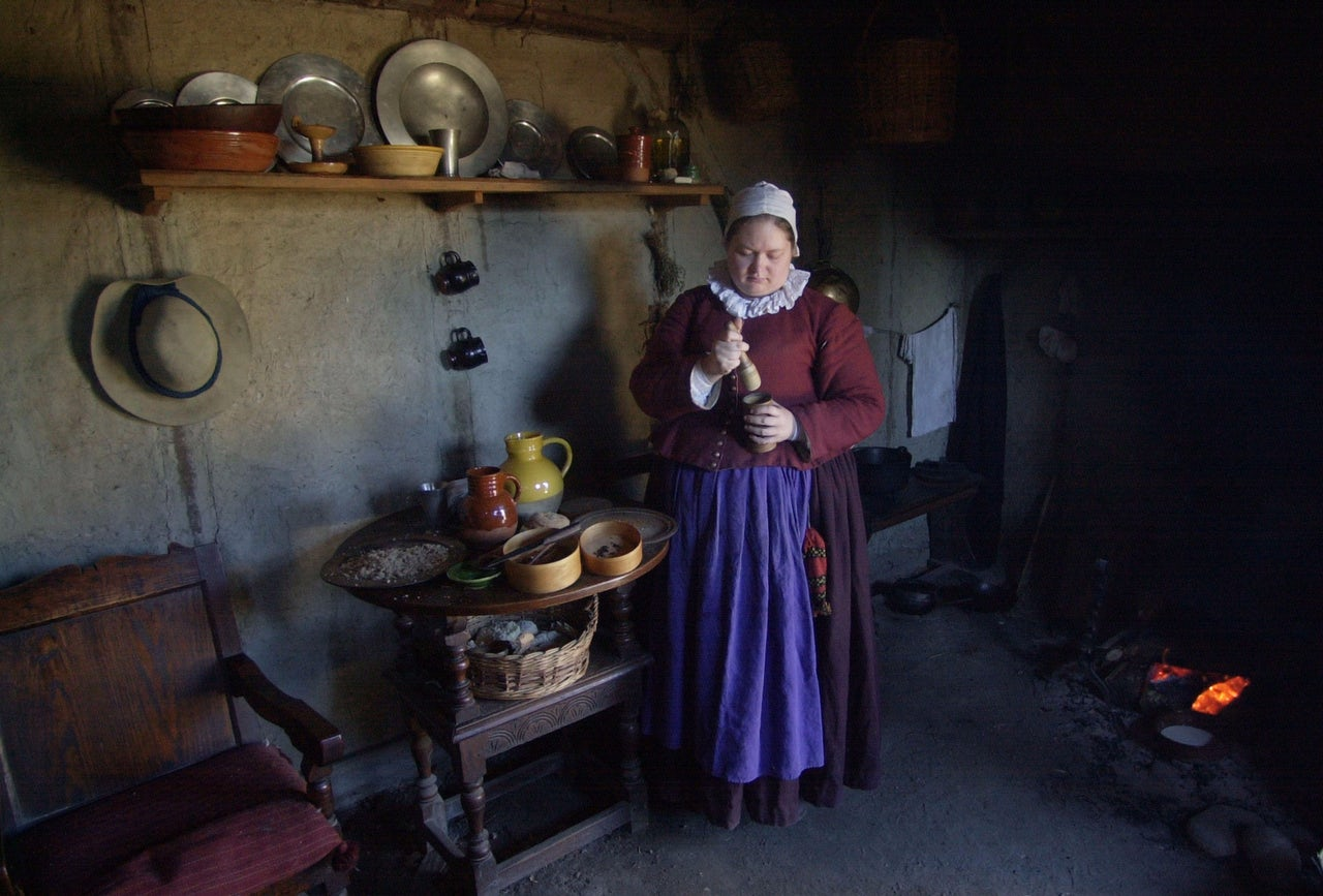 An interpreter prepares fritters in her one-room house at Plimoth Plantation in 2003.