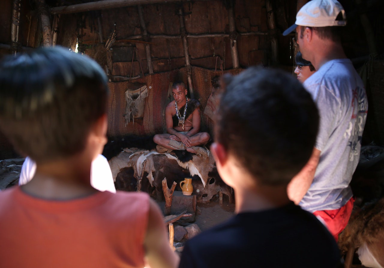 Visitors listen to an interpreter at the Wampanoag Homesite.