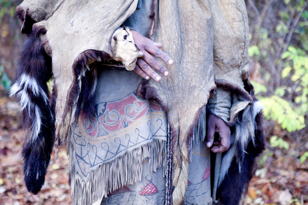 A woman wears a cloak made of skunk skins over her deerskin dress at the Wampanoag Homesite.
