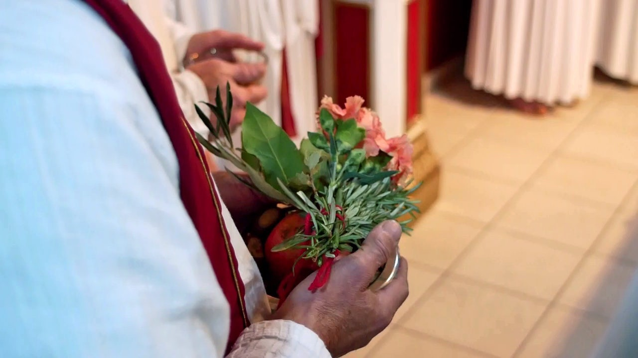 A priest holds flowers as offerings to the gods.