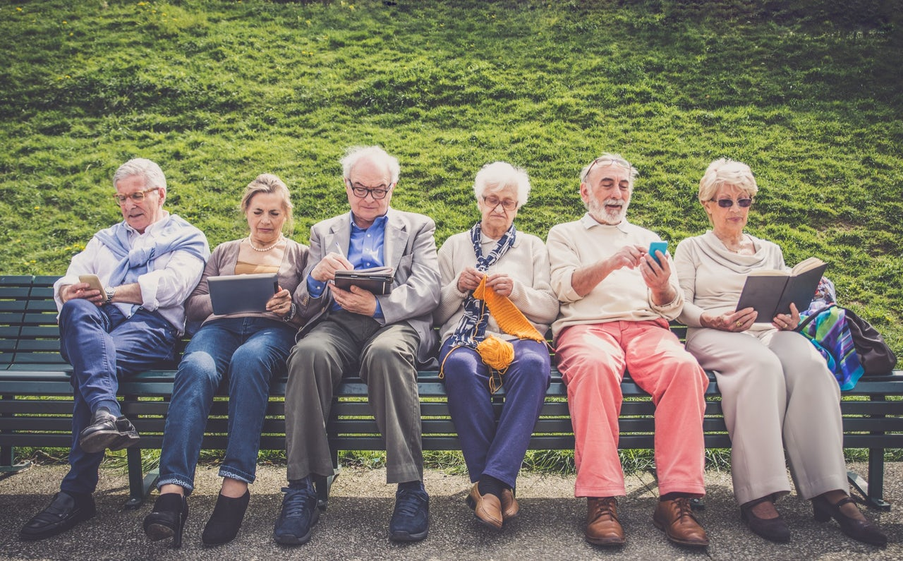 group of elder people sitting on a bench