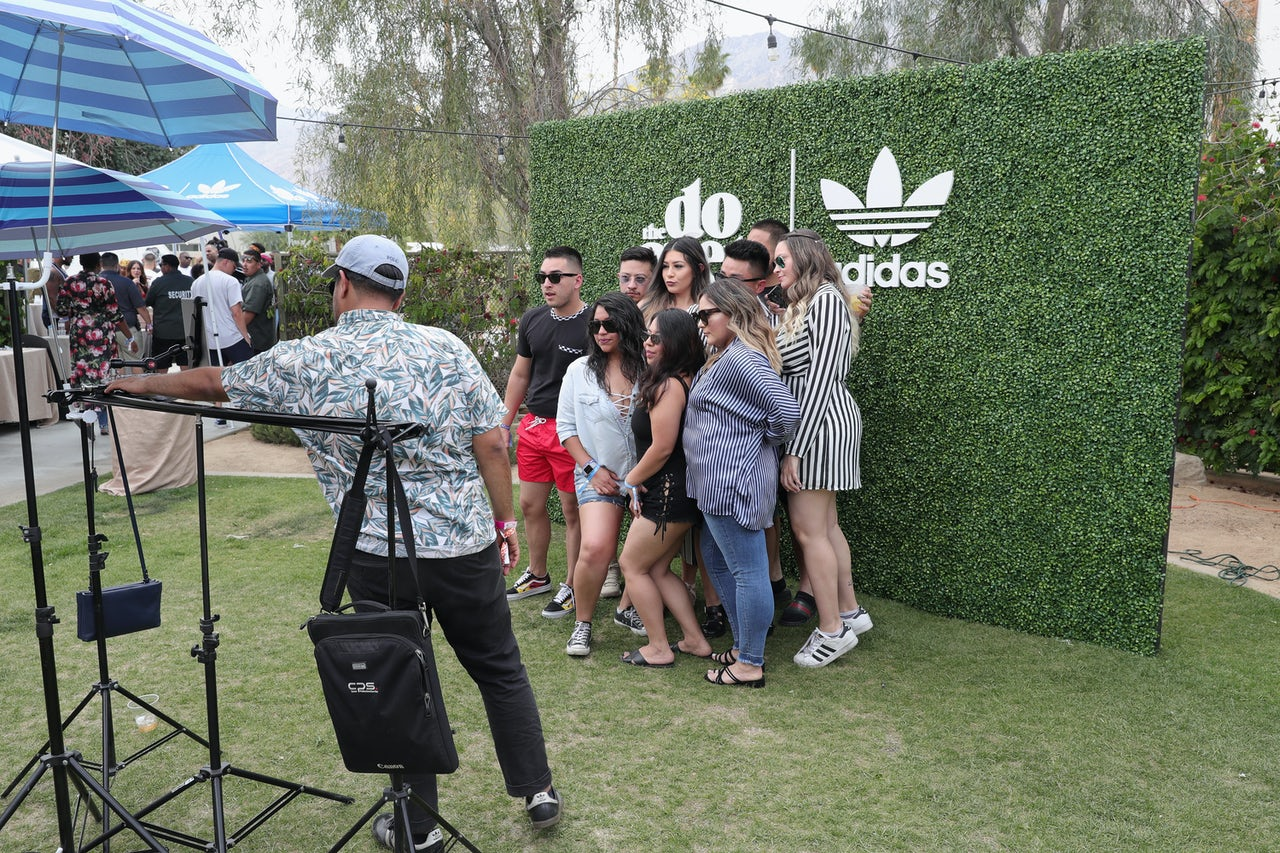 A group of Coachella-goers pose in front of an adidas logo.