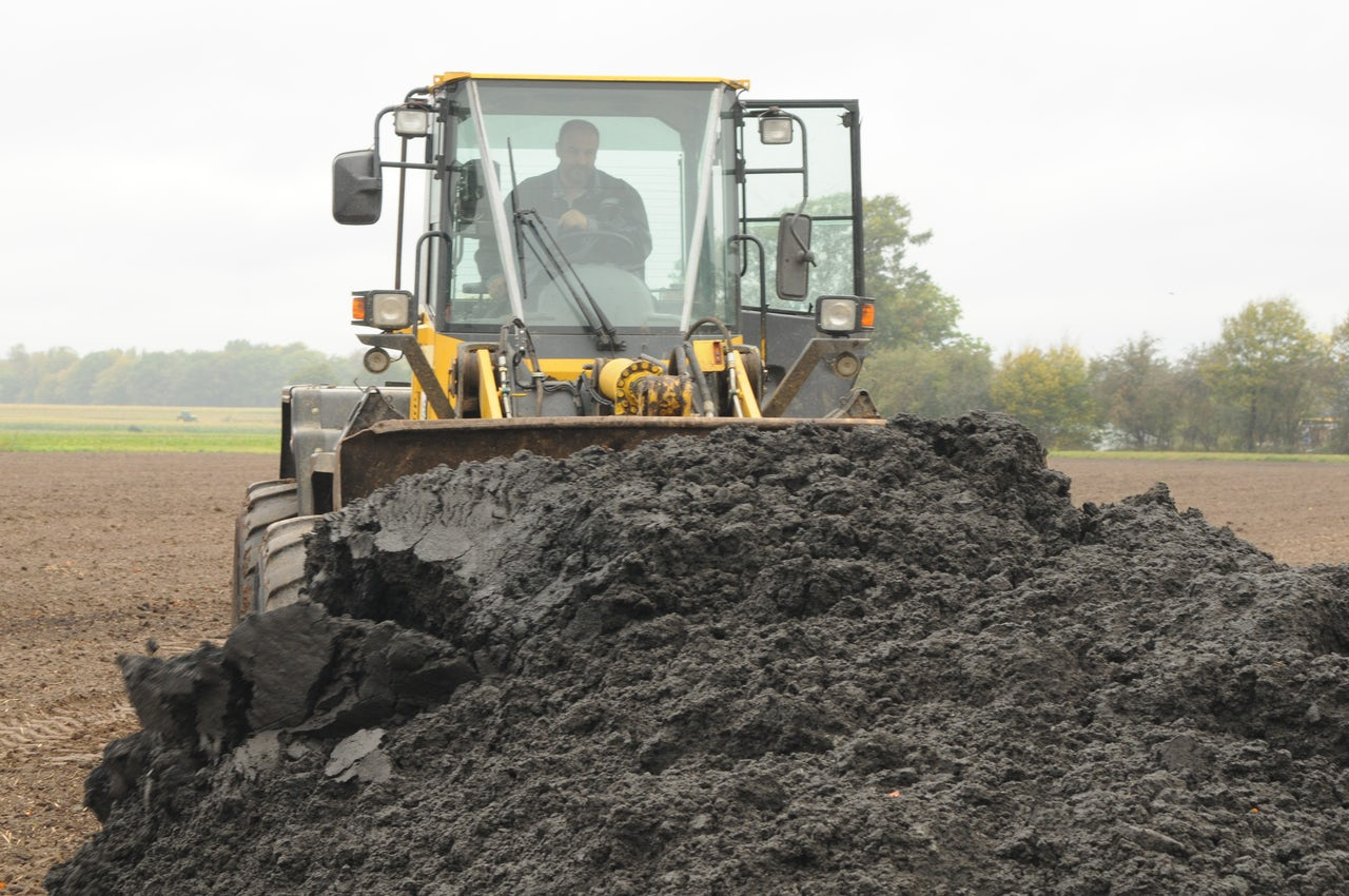 A man pushing a mass of sludge with an earth mover.