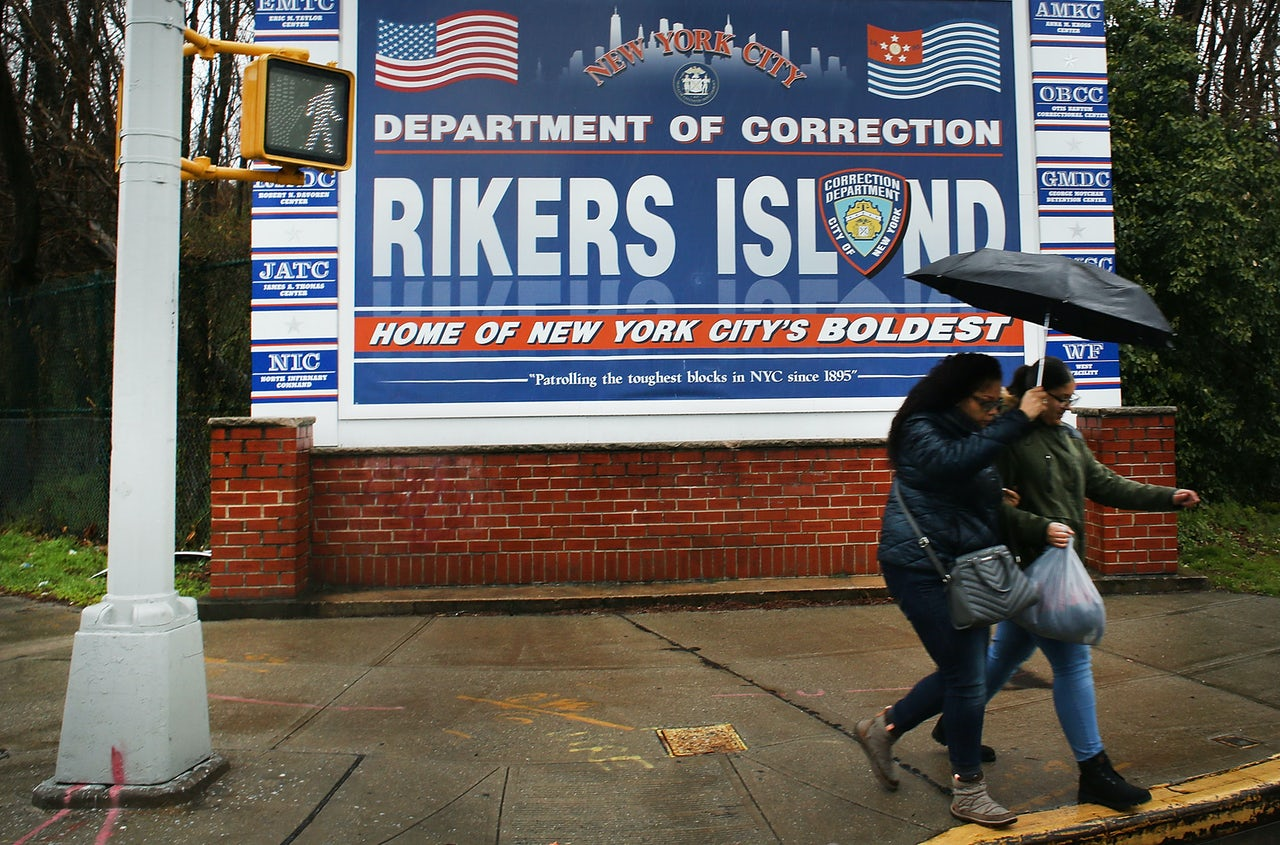 People walking by the entrance to Rikers Island, 2017.