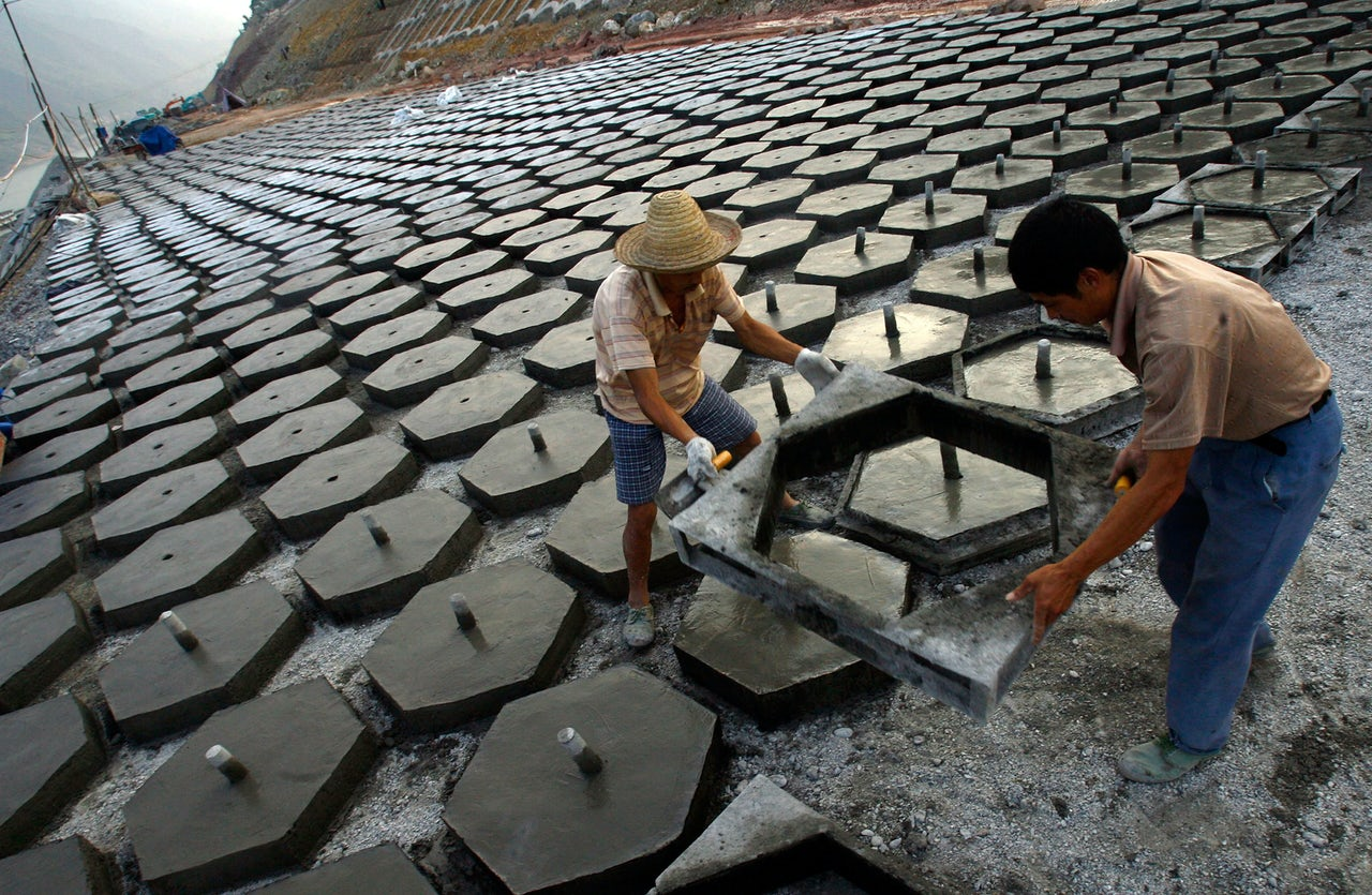 Workers pour concrete forms in an effort to harden the cofferdam of the Three Gorges Reservoir in China. Cement is the second-most consumed material in the world, after water.