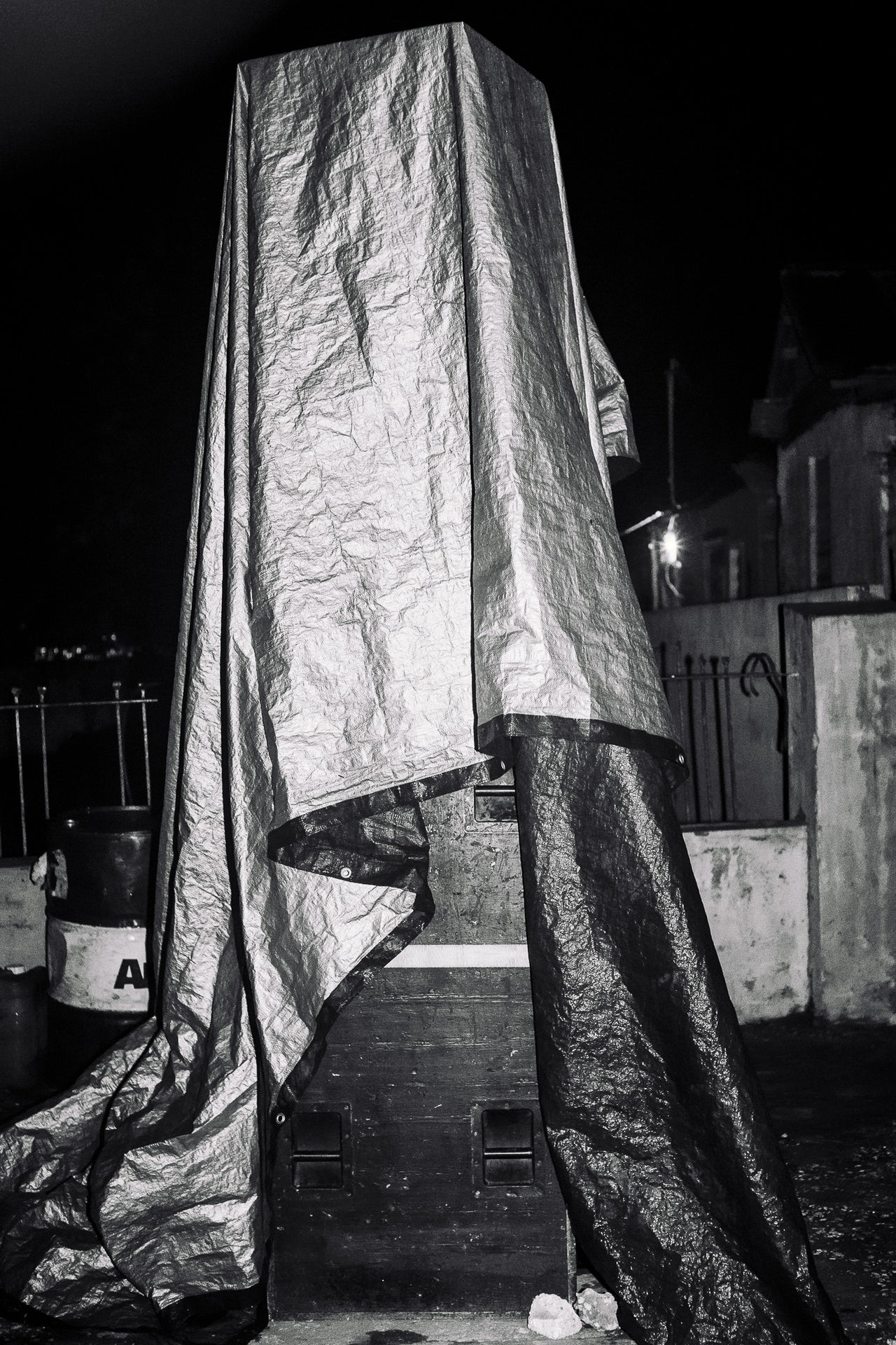 A custom hand made speaker stack for the sound system Presto Mix, tarped against impending rainfall at 1 AM before the beginning of Day Rave Thursdays, a popular weekly party in Greenwich Farm, Kingston. The party usually starts around 3 AM and runs until well after sunrise.