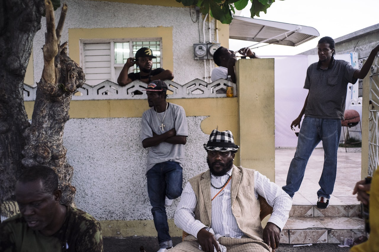 Baby Demus (center) sits outside of the home studio of Pliers, another local star, in Portmore. Kingston and Portmore are home to hundreds of small recording studios, many owned by artists, who mentor and support a cadre of performers, producers and musicians.