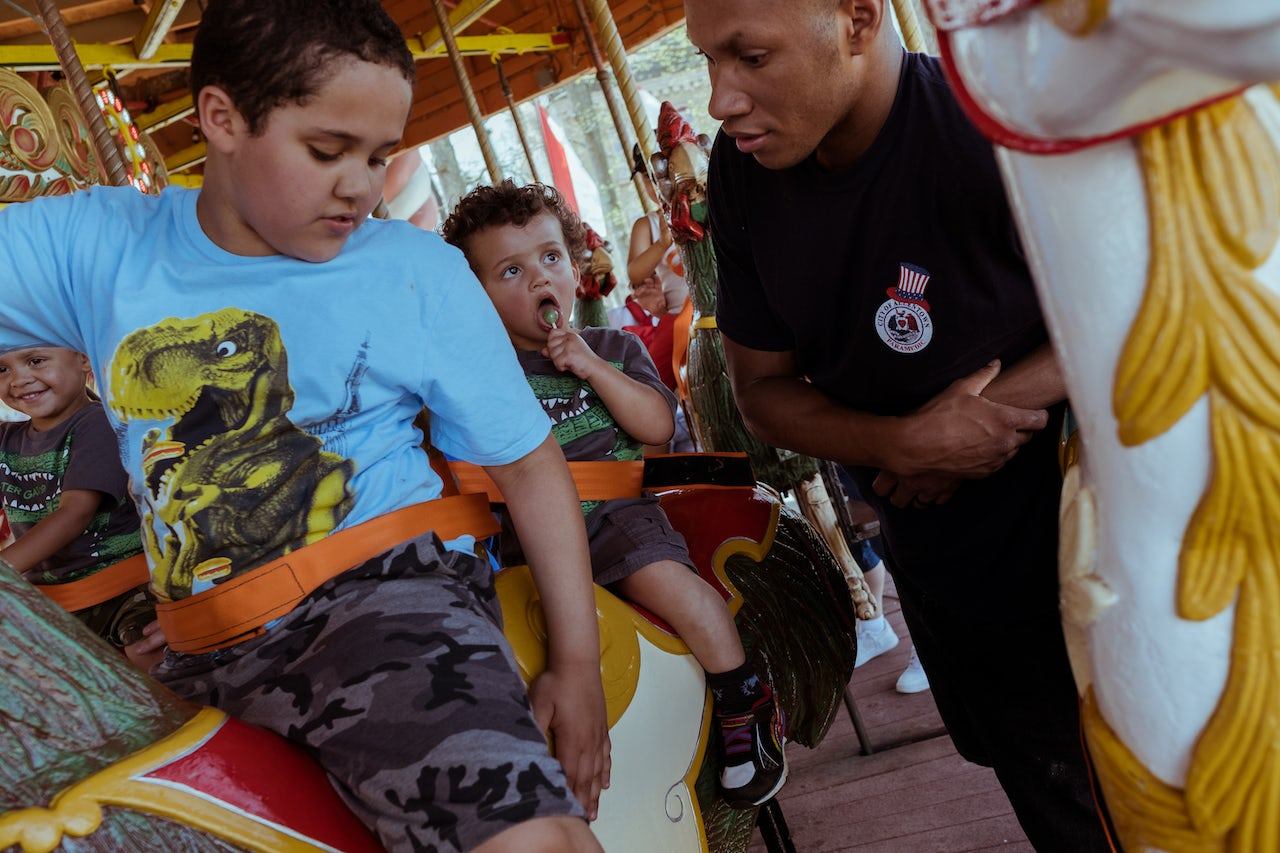 Young children donning brightly colored dinosaur shirts share a relaxing moment on the the Six Flags Columbia Carousel, accompanied by an adult.