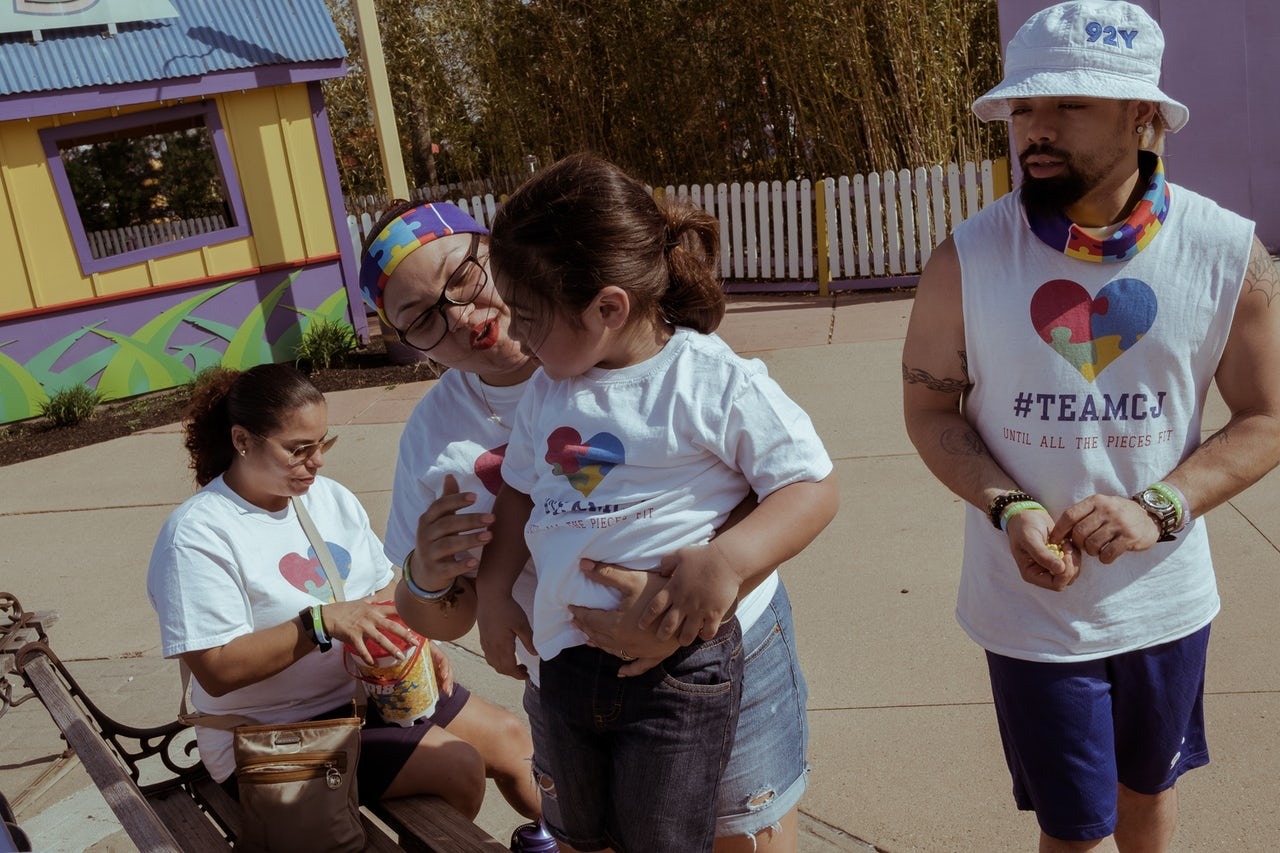 A family wearing matching #TeamCJ shirts share a moment on a park bench. Some families conduct fundraising for autism research and treatment, using team names dedicated to the name of a loved one who has autism.