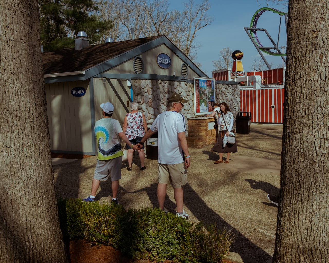 A man and a young boy hold hands outside of a restroom adjacent to the Bizarro roller coaster.