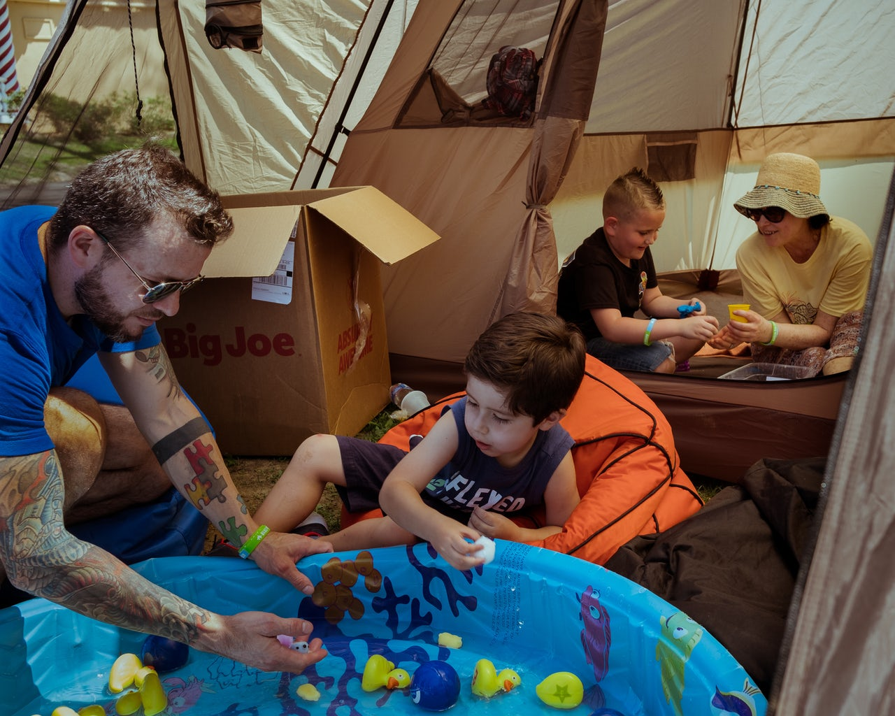 In a waterside Decompression Tent by the Six Flags Fantasy Forest, a man shares a moment with a young boy. The multicolored puzzle tattoo pattern on his forearm represents autism awareness.
