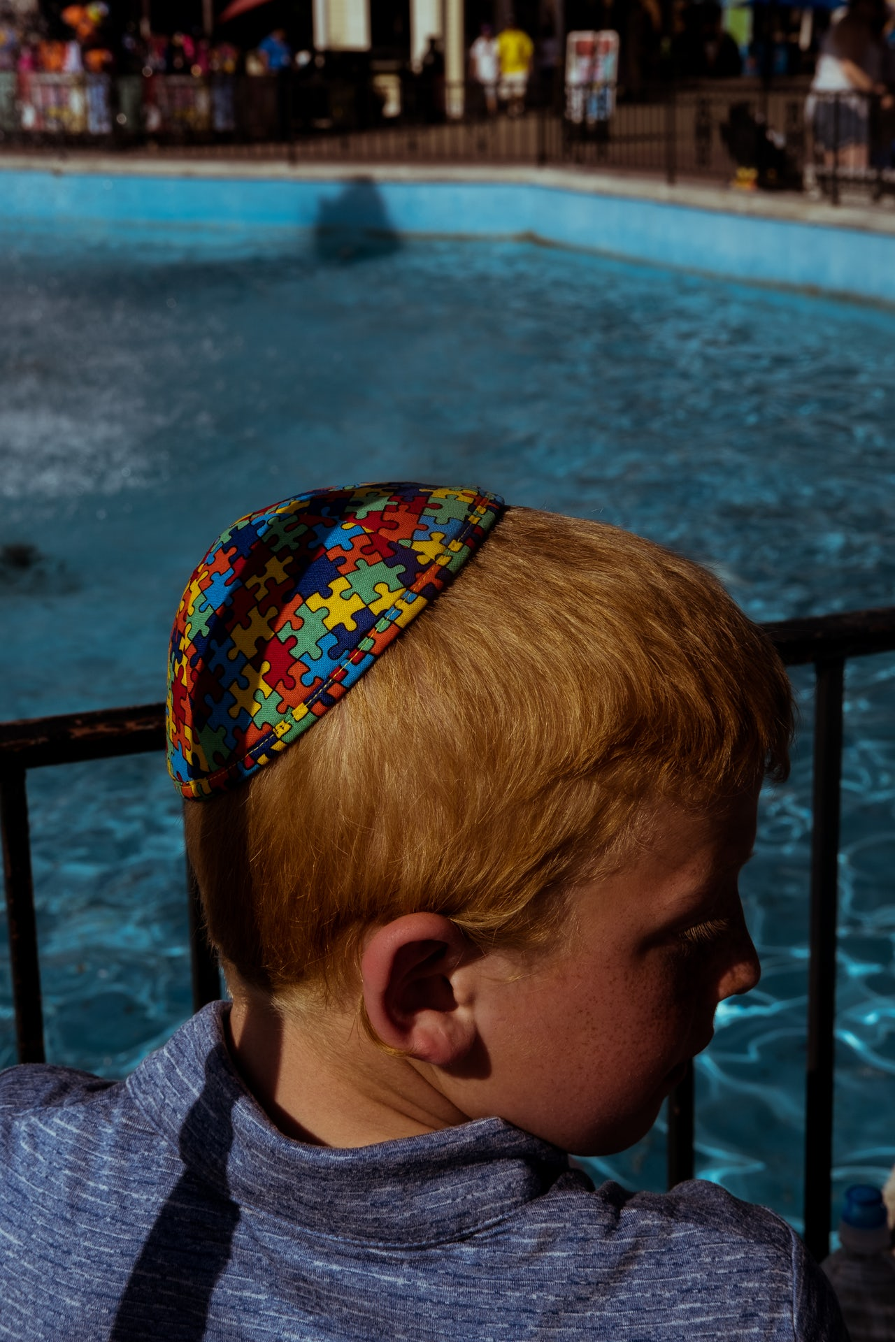 A young boy stands beside the Main Street Fountain, located near the entrance of the park, wearing a kippah bearing the multicolored jigsaw pattern that represents autism awareness.