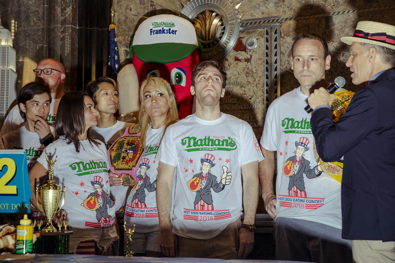 "The competitors, including Joey Chestnut (right, facing the camera) pose during a ""weigh-in"" at the Empire State Building."