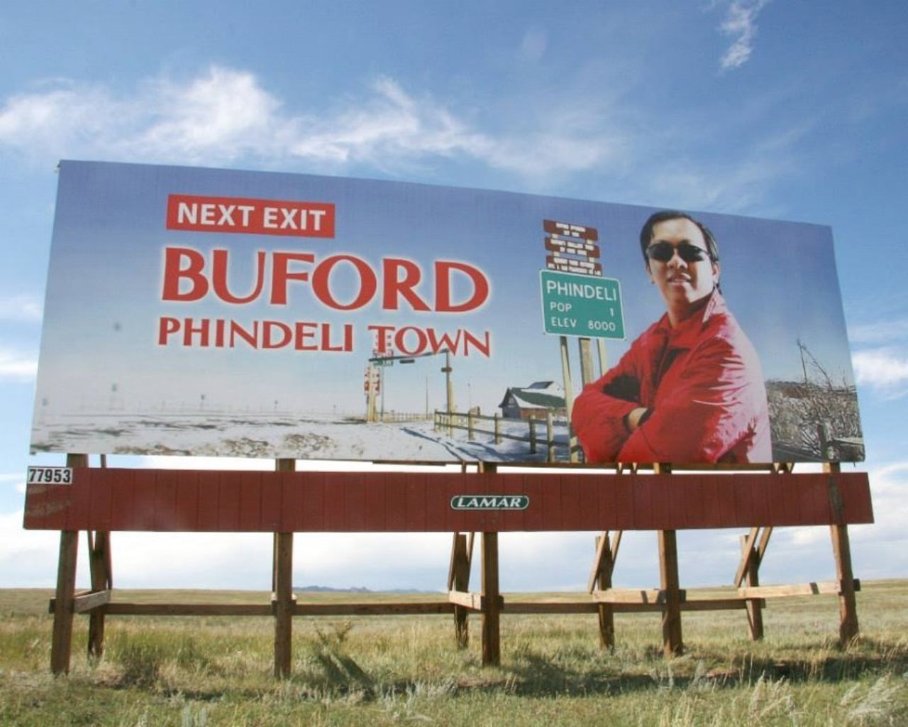 The owner of PhinDeli Town Buford poses on the town's welcome sign