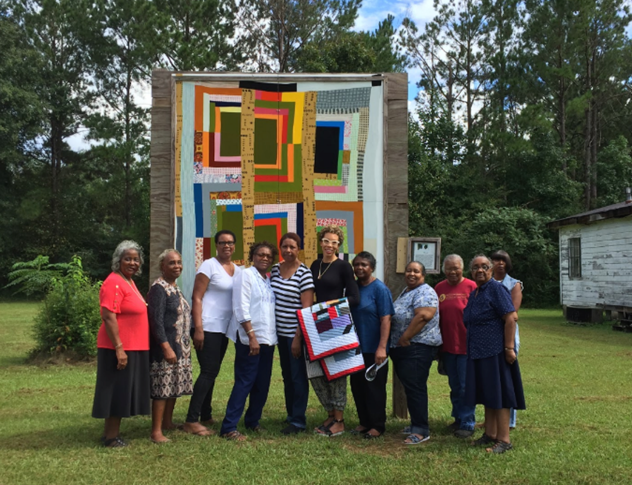 Members of the Collective pose with Amy Sherald (holding a quilt). Behind them is a painted mural based on a quilt Mary Ann Pettway's mother made.