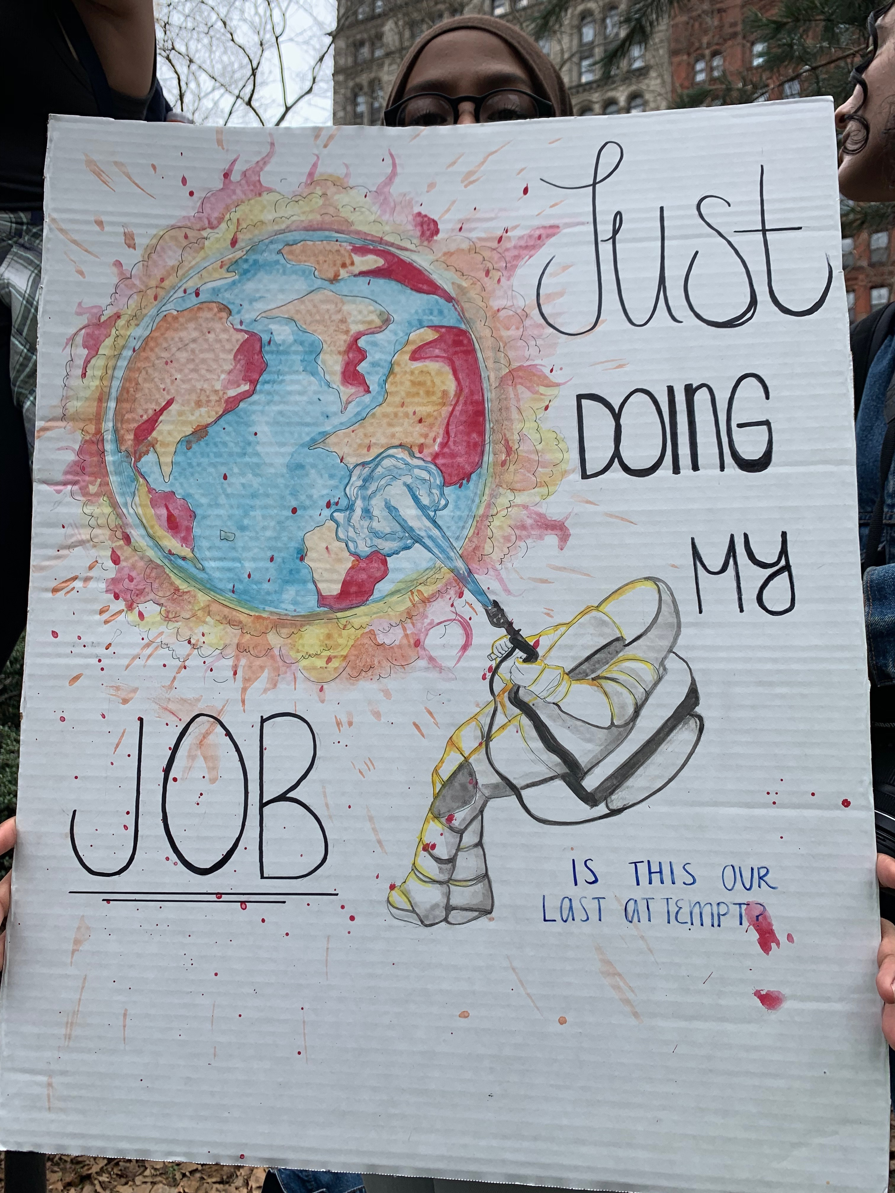 A student shows off their poster in City Hall Park.