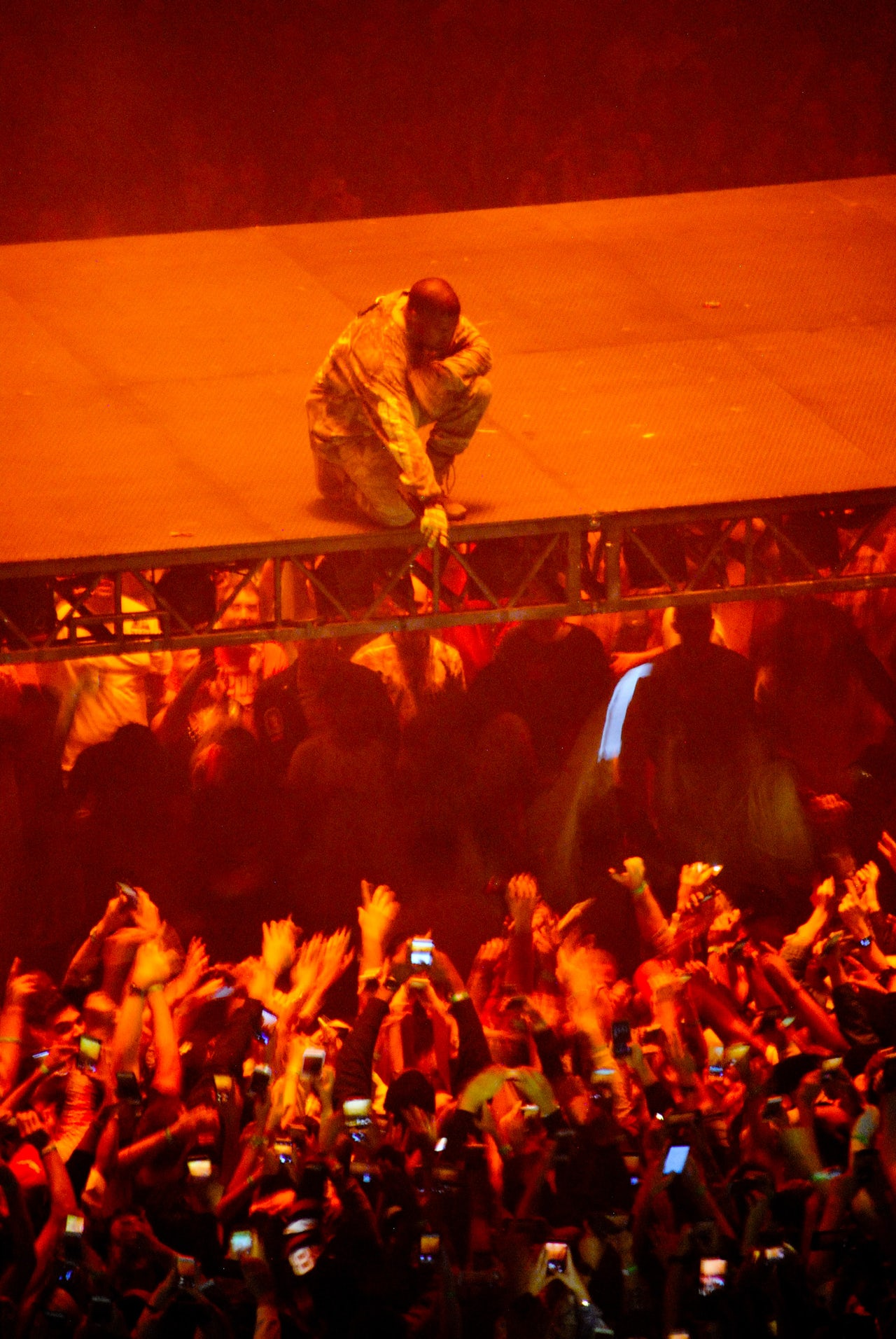 Kanye reaching down to fans at a tour stop in Los Angeles.